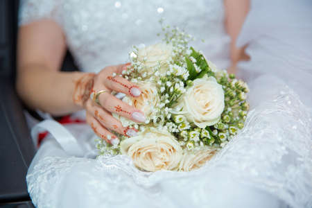The bride sat in her car and put her hand on the white wedding flower . The bride is wearing white pants