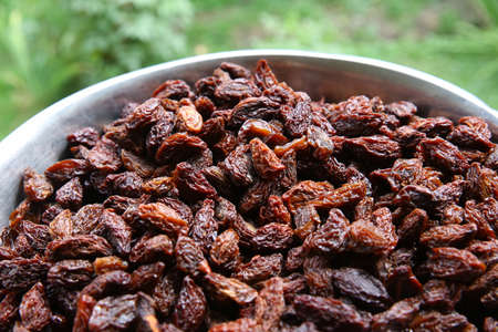 Many Raisins for background grape raisin texture .black raisins in the tray . Sweet dry raisins close-up shot for green background Banco de Imagens