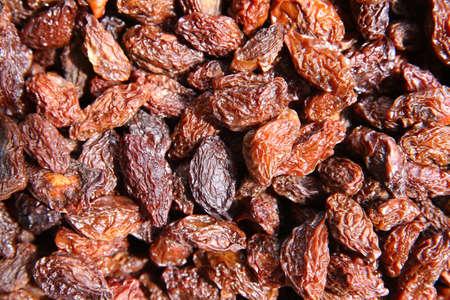 Many Raisins for background grape raisin texture .black raisins in the wooden bowl. Sweet dry raisins close-up shot for background