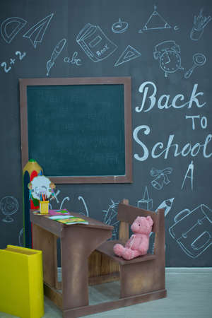Back to school. Happy smiling pupil drawing at the desk. class room with blackboard on background. Alarm clock, pencils, books. first day of fall.Back to school concepty with writing on blackboard