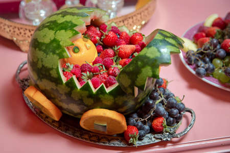 A chariot carved with strawberry watermelon in a decorated watermelon. Inside the plate, the raisins, oranges and grapes.