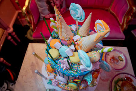 Colorfull cake pops in waffle cone for ice cream in assortment, decorated with confectionery sprinkles on white wood table. blue cake with colorfull small sweet ball . decoration for cake and bekery.