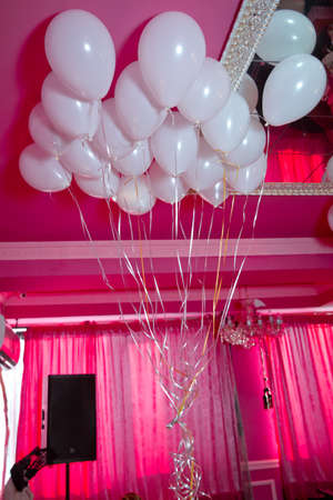 white balloons float on the white ceiling in the room for the party. Wedding or children birthday party decoration interior . Helium balloons red float.
