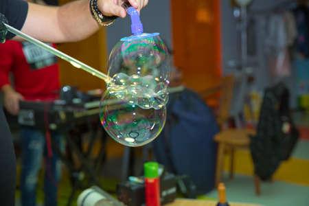 Soap bubbles show. Children's party. To burst the soap bubble