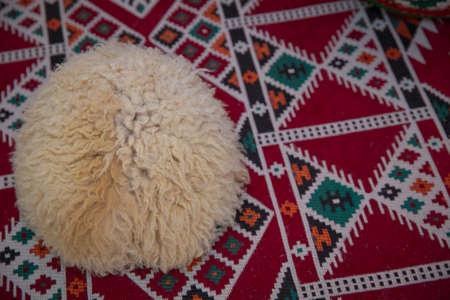 羊毛山の帽子、美しい山羊の帽子、カーペットの背景に羊皮帽子。羊毛で作られた白人の人々の頭飾り。コサックハット