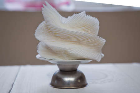 White napkins in metal bowls brown background . The napkin is wrapped in a bowl . The napkins are twisted and designed .