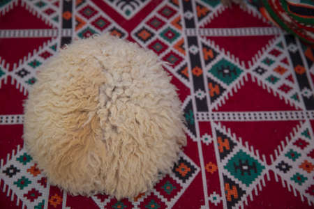 sheep wool mountain hats,beautiful mountain sheep hats,sheepskin hats on a background of carpet . Caucasian peoples headdress made of sheep wool. Cossack hat