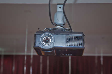 Black Projector hang on white ceiling in big meeting room or university. A white overhead projector on ceiling indoors. Modern video projector on ceiling in room Stock Photo