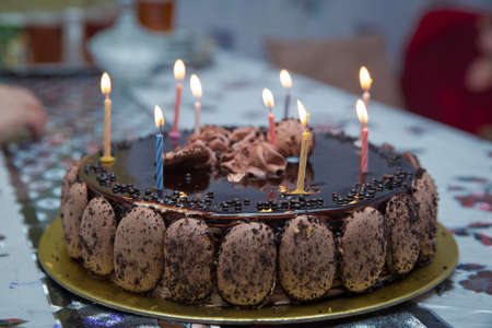 Delicious vegan chocolate cake. Selective focus. Super chocolate cake with chocolate sauce . Piece of chocolate cake with icing . The cake candles are lit .