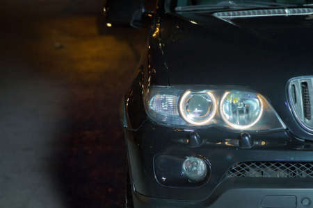 Macro view of modern car xenon lamp headlight, bumper, wheel. Exterior of a modern car . Black dark luxury car in the night road with angry bright headlight front for wallpaper and background .