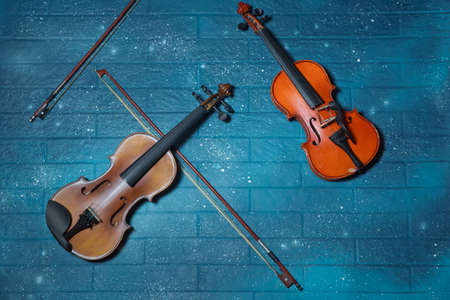 Red and brown Violin and tar blue in the background.Violin in front of blue brick wall .Classical music concert poster with orange color violin on blue background with copy space for your text