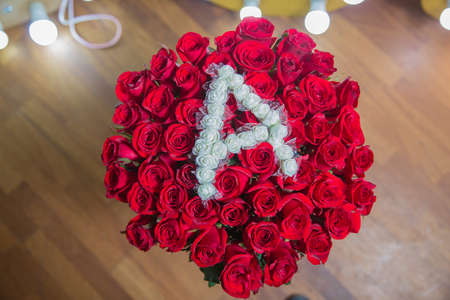Beautiful rose flower in garden. Rose wooden background. Roses flower texture. Red rose. Bouquet of red roses. copyspace . The letter A is written with white flowers.