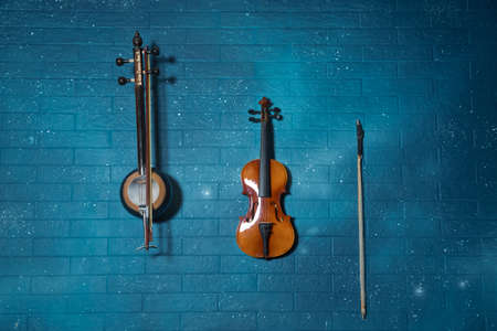 Violin and tar blue in the background.Violin in front of blue brick wall .Classical music concert poster with orange color violin on blue background with copy space for your text Reklamní fotografie