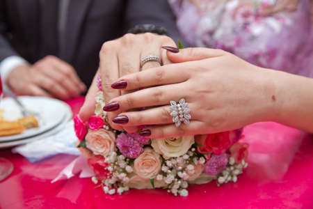 Colorfull Wedding flowers . Bride and groom with Engagement gold rings put on the table, and next to them lies a wedding bouquet . red table .
