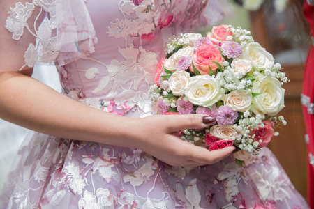 Wedding couple holding hands .Bride and groom hands with wedding white flowers and pink bridal dress . Bride and groom's hands with wedding flowers .