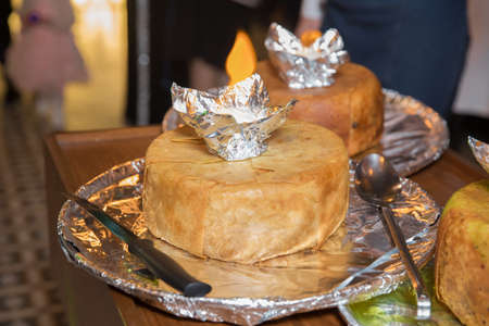 Shah pilaf. Khan pilaf in a pita. Traditional oriental dish on tableware Azerbaijan with fire on a table in restaurant .the chef cuts off the drill and puts it on the plate