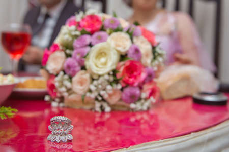 Colorfull Wedding flowers . Bride and groom with Engagement gold rings put on the table, and next to them lies a wedding bouquet .red table . Wedding rings next to a flower bouquet selective focuse 스톡 콘텐츠