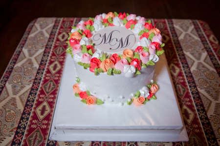 Cake with white, colorful round top. Above the MM inscription. On the background of the carpet.