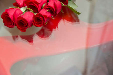Bouquet of flowers in the opposite mirror . Bridal bouquet. Reflection of a wedding bouquet in glass, mirror. Flowers lie on the table. A flowers arrangement of rose rosettes on a glass table . Drop Banque d'images - 140629756