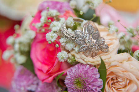 Bride and groom with Engagement gold rings put on the clorfull wedding bouquet .close up wedding ring on top of a colorfull bouquet. . macro .Close up of wedding rings on the bouquet . Macro