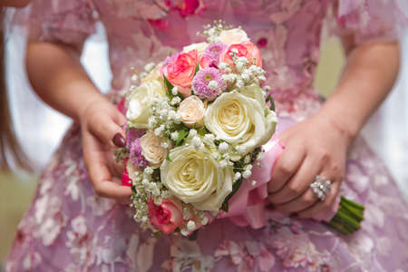 Wedding couple holding hands .Bride and groom hands with wedding white flowers and pink bridal dress . Bride and groom's hands with wedding flowers . Banque d'images - 140644543