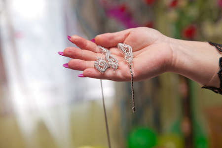 Luxury pendant on the neck in the hands of the girl.Female treasures. Necklaces, rings, earring in female hands on blurred background. Hand Holding Diamond Bracelet