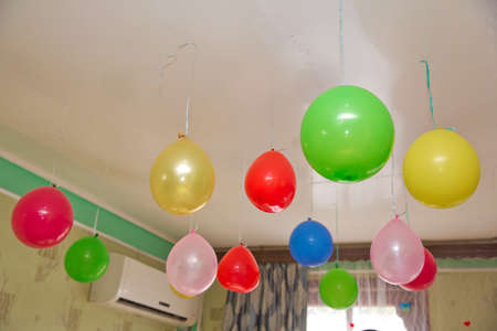 Helium balloons . Colorfull and red balloons float on the white ceiling in the room for the party. Wedding or children birthday party decoration interior . 스톡 콘텐츠