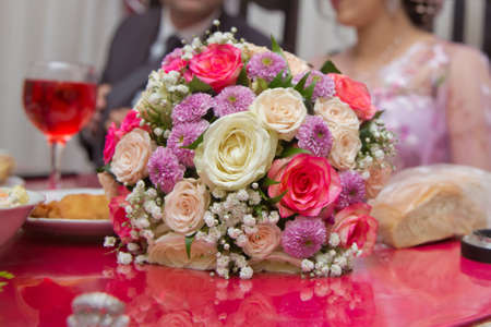 Colorfull Wedding flowers . Bride and groom with Engagement gold rings put on the table, and next to them lies a wedding bouquet .red table . Wedding rings next to a flower bouquet selective focuse Reklamní fotografie
