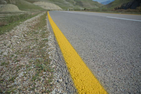 Mountain road in poor condition, has been repaired by patching several times .Winding country road in mountains . Asphalt road in the mountains with soft sky on the background. yellow and white line Stok Fotoğraf