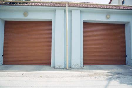 Automatic Electric Roll-up Gate Or Push-up Door In The Modern Building Ground Floor . Shutter door or roller door and concrete floor outside . Brown Automatic shutters in a house . gates in the garage