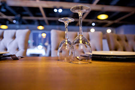 empty inverted glass on the wooden table .Empty outdoor restaurant table, Inverted empty glasses on the table. Tableware on table in cafe, focus on bakal stem .