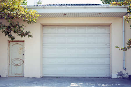 Automatic Electric Roll-up Gate Or Push-up Door In The Modern Building Ground Floor . Shutter door or roller door and concrete floor outside .White Automatic shutters in a house . gates in the garage