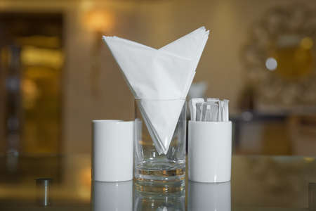 A table in a cafe or restaurant. White napkins in a metal napkin holder, spices salt and pepper on a woodeglass table, panoramic view. toothpick