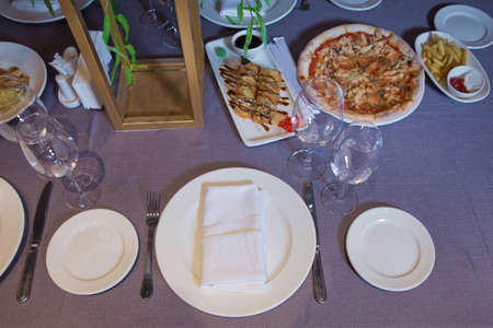 empty glasses and plates on the table in the restaurant . Tables set for meal . fork, knife , table towel . Pizza, potato fries.
