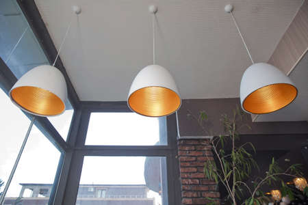 Close up incandescent lamp shining, Yellow light of lamp hang on ceiling . Ceiling light retro style hanging from ceiling of industrial modern restaurant