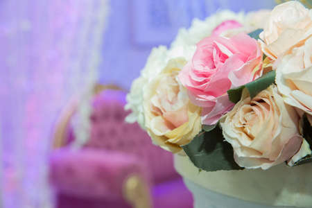 Beautiful pink and white flowers on table in wedding day . wedding table, wedding decorations . Large vase with beautiful roses stands on rich served dinner table .Wedding flower composition for guest