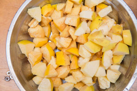 Quince fruit is cut into large pieces, composed in metallic heat resistant pot, bake, standing on a wooden chopping board .