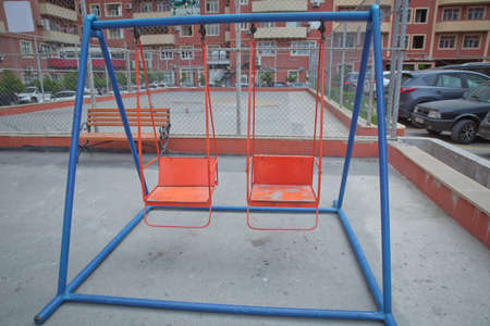 Childs swing in a park . Wooden and Empty red and blue chain swings in children playground . chain swings hanging in garden .