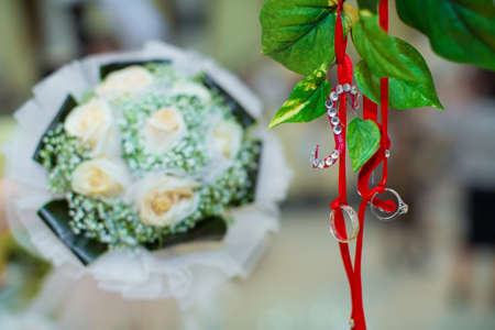 Two wedding rings hung from a tree branch . The rings hung from a red ribbon. Wedding bouquet in the background