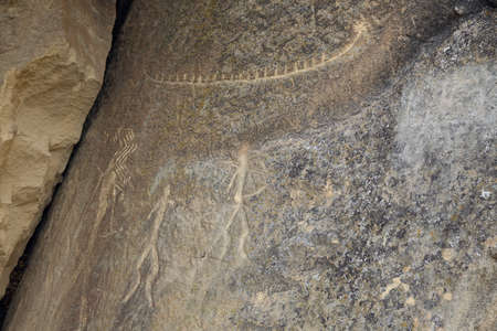 Ancient rock carvings petroglyphs of people with boat in Gobustan National park. Exposition of Petroglyphs in Gobustan near Baku, Azerbaijan.
