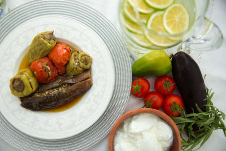 Stuffed eggplant in the plate . Eggplants are stuffed with meat lamb and rice. Patlican . eggplant filling . Eggplant, peppers, tomatoes . Yogurt in a brown bowl . Chopped lemon in a glass jar .