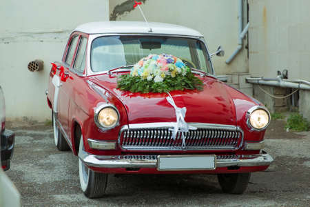 Wedding bouquet on vintage wedding car . Unusual front headlight, old burgundy red car for any purpose . Red vintage wedding car parked .
