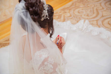 Bride writing her shoe with a pencil . Bride writes under shoe wedding ritual superstition . hand of a bride writing single friends name under her shoe before wedding