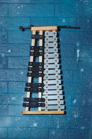 Glockenspiel, also known as orchestra bells, is arranged with metal bars similiar blue wall . Marching Bell with Wood . practice bell lyre instrument in marching band