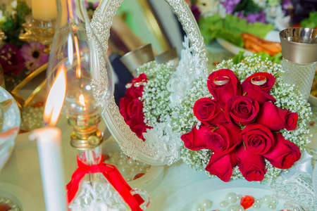 Kerosene oil lantern lamp . Red ribbon . Red engagement flowers on white table . Bride and groom with Engagement gold rings put on the red wedding bouquet . The mirror of the rose is mirror
