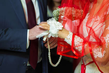 The brides is wearing a ring on the bride's hand . room Dresses the Ring for the Bride, close-up. Newlyweds exchange rings, groom puts the ring on the bride's hand in marriage registry office Foto de archivo