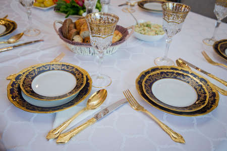 Beautifully decorated table with gold plates, linen napkin , spoon, fork . Empty plate , gold set on wooden white table . Banque d'images