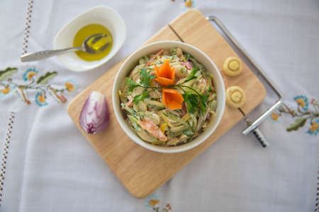 Salad with ham, red and orange pepper, mushrooms, pickles, white sauce, on a white bowl and olives. Chopped red onion . olives on a small white bowl . wooden board Foto de archivo