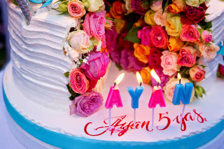 Two-layer cake . Wedding cake decorated with colorfull roses. Celebration party concept. flowers in the middle of the place where the cake is cut on the blue butterfly . White cake with rounded .
