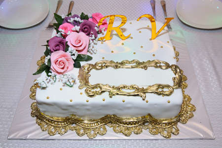 White rectangular cake. A place to write on the cake. The letters R and V in yellow. Pink flowers on top of the cake.